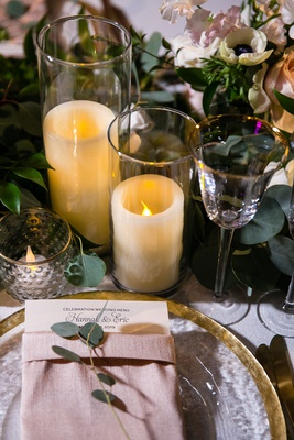 wedding reception flameless candle gold rim glassware charger plate pink napkin greenery eucalyptus