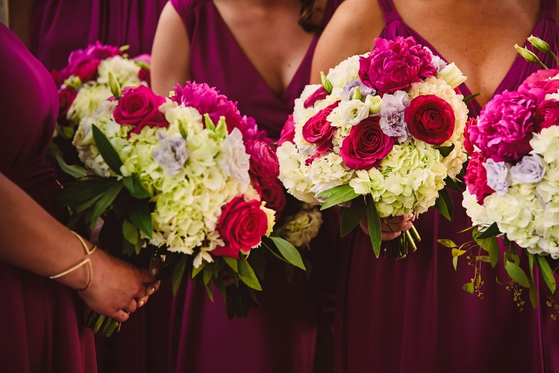 Bridesmaids in magenta bridesmaid dresses holding bouquets ivory hydrangeas and pink rose peonies