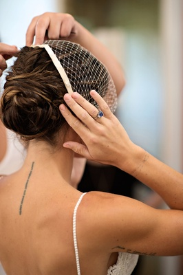 Bride with updo and sapphire, diamond engagement ring puts on birdcage veil