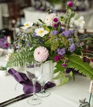 Wedding reception Lyndsy Fonseca and Noah Bean ferns purple flowers purple napkin wood chair