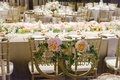 bright florals featuring white pink and orange flowers cover white table linens and gold chairs