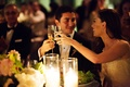 Bride and groom look into each other's eyes and cheers clink glasses at wedding reception toast