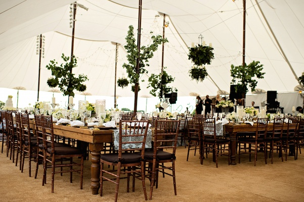 Tented wedding reception with country tables, branches with leaves on posts, and greenery chandelier