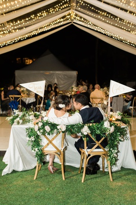 Wedding reception tent sweetheart table bride groom kiss flags garland white blush flowers kiss