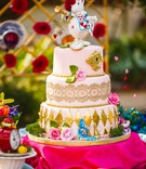 alice in wonderland cake with gold details and white rabbit cake topper
