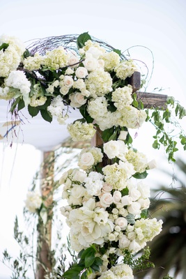 corner wooden chuppah white flowers greenery rustic seaside wedding ceremony vines