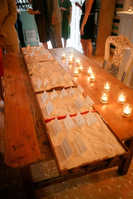 Wood table with candles escort cards in boxes filled with white sand destination wedding