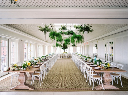 Wedding reception sunlit ballroom two long wood tables ferns in macrame planters hanging ceiling