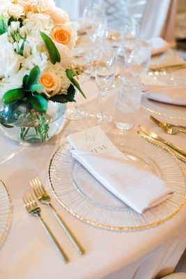wedding reception place setting beige linen gold rim charger gold forks knives small centerpiece