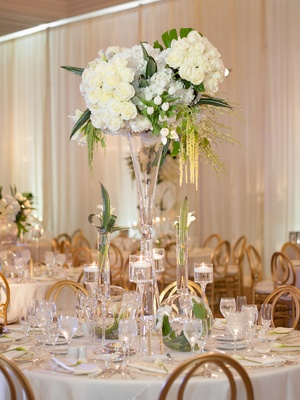 Round table with tall white centerpiece green leaves tropical amaranthus gold chairs floating candle