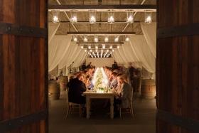 Guests in vineyard wine barrel room at long table