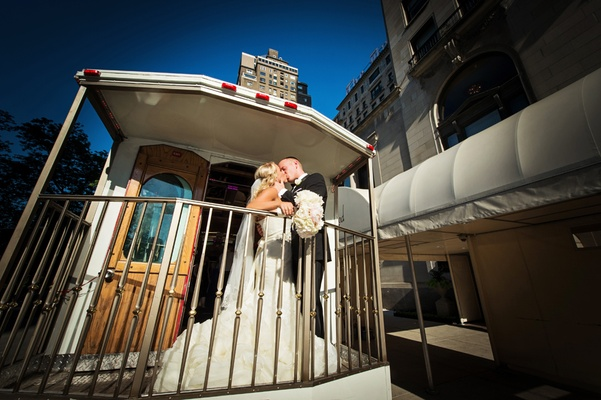 bride in vera wang, groom in vera wang, newlyweds kiss on back of trolley in chicago