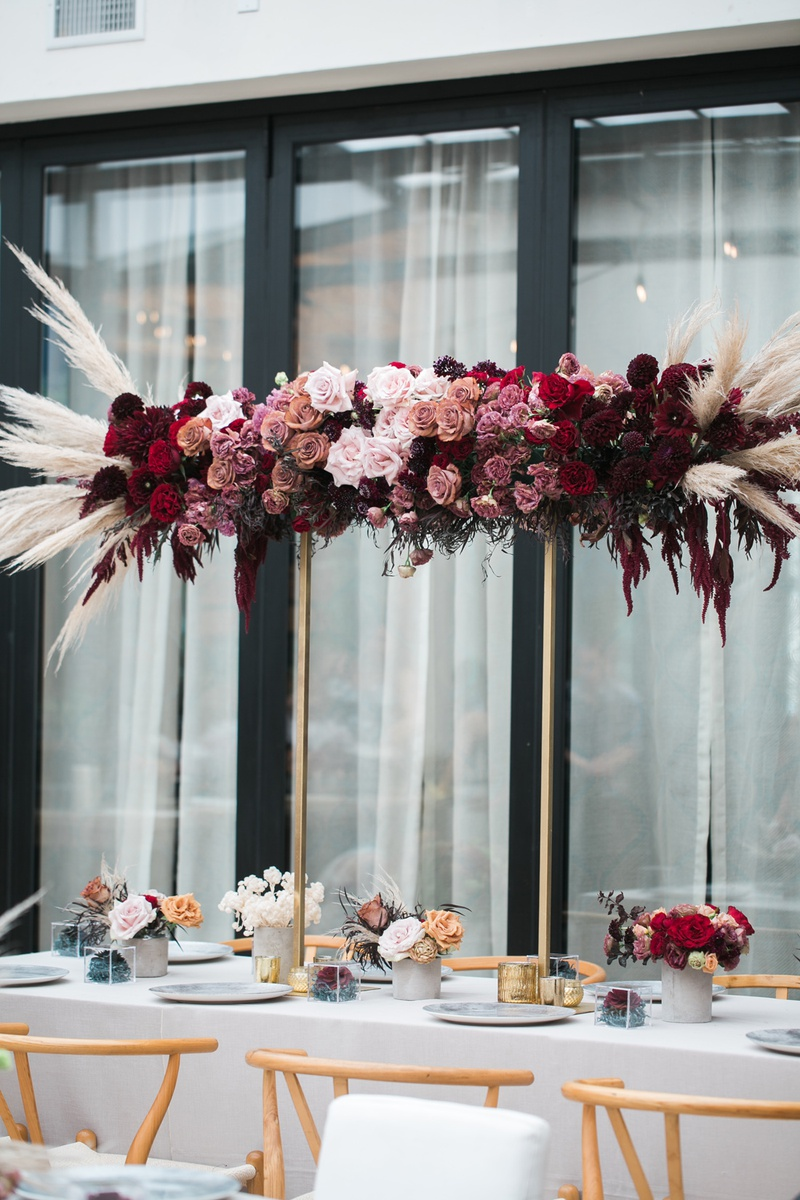 burgundy, red, mauve roses with pampas grass on gold stand