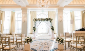 indoor ceremony with arch of greenery and white flowers, white drapery