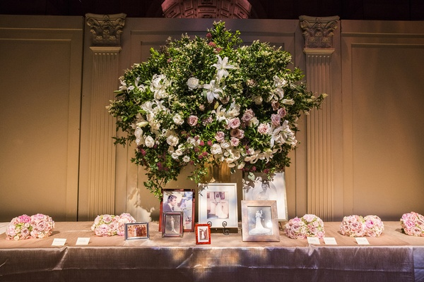 Escort cards on long table with framed family wedding photos