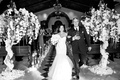bride and groom recessional with trees wrapped with orchids, dripping with jewels, as ceremony decor