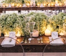 Ghost chairs around wood table with candles