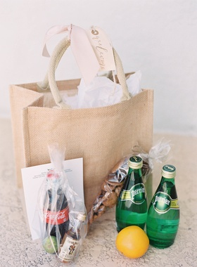 Burlap welcome bag with tag and ribbon coca cola captain morgan perrier bottles snacks lemon