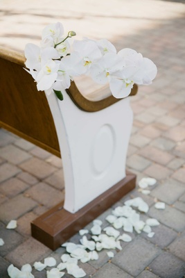 white orchids accent ceremony pew bench seating