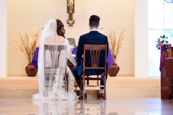 Bride and groom sit in wooden chairs at Catholic ceremony