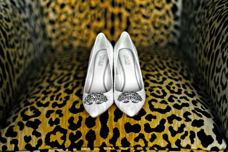 Leopard Print Chair Displaying White Wedding Shoe Pumps With Brooches On  Toes
