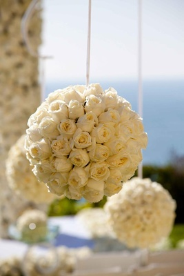 White ribbon suspending rose pomander balls at wedding ceremony