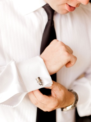 Groom putting on shirt with black tie and silver skeleton skull top hat cufflinks