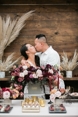 bride and groom kissing at bridal shower after groom delivers flowers