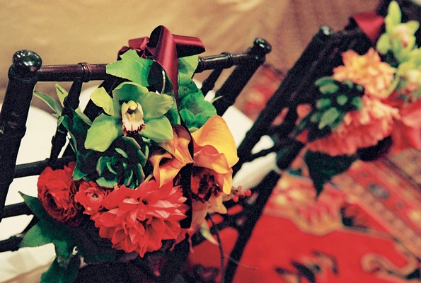 bundles of red yellow and green flowers tied to chair backs with red ribbon