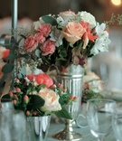 Low centerpieces in silver vases with pink and white flowers