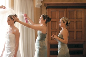 Bridesmaid helping bride with hair in bridal suite