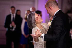Mother of the groom in Adrianna Papell gold sequined outfit, knit sweater dances with groom in black
