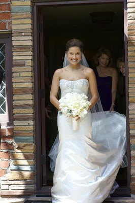 Bride walks out of suite in white bridal gown with bouquet