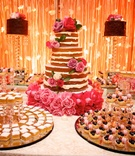 table of sweet treats at wedding reception in colombia tarts and cake with floral decorations