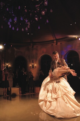 Bride in ball gown is dipped by husband on dance floor