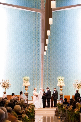 Bride and groom at altar with tall flower arrangements