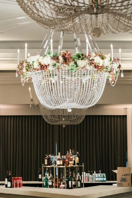 crystal chandelier with floral accents suspended over the bar at reception for 50th anniversary