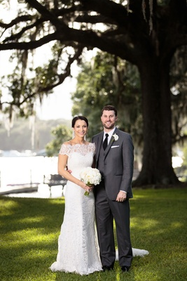 bride in lace, off-the-shoulder Anna Maier and groom in charcoal grey Men's Wearhouse suit