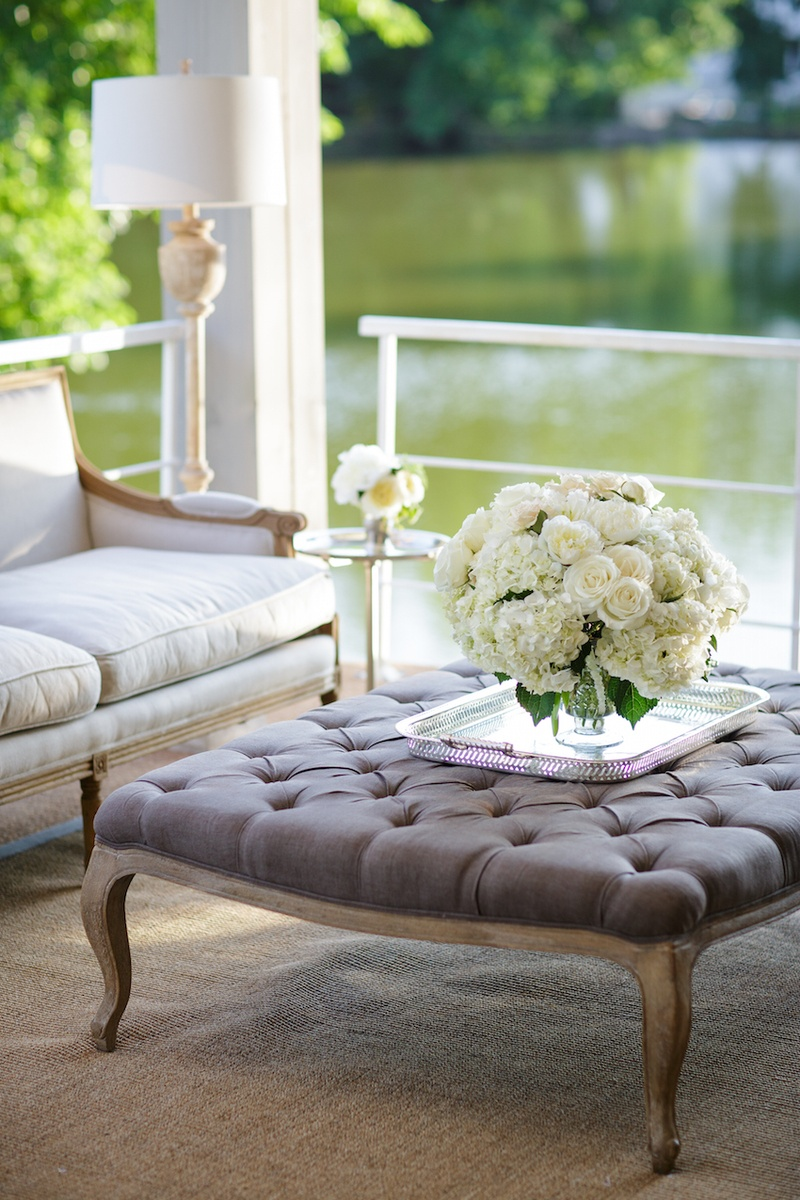 Reception lounge area with a grey tufted top wood table, vase with white roses, hydrangeas, peonies