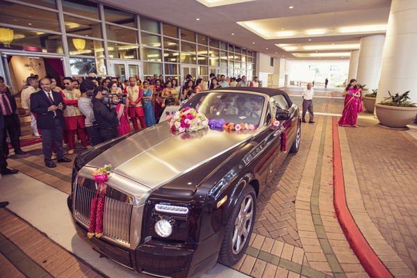 south indian groom arrives to wedding reception in luxury car decorated with flowers