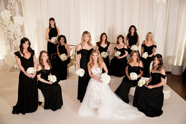 Bride in mira zwillinger wedding dress black bridesmaid dress with white bouquet ruffle off shoulder