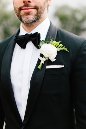 Groom boutonniere with white flower light pink ribbon and greenery white pocket square black bow tie