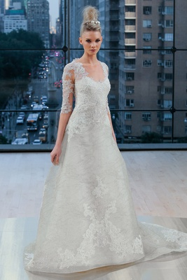 ¾ illusion sleeve A-line gown with beaded lace appliqués, heart shaped illusion back and chapel trai
