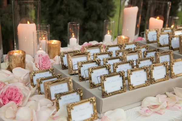 Framed seating cards surrounded by candles and petals