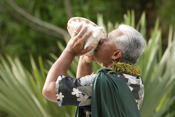 A conch shell blower at a Hawaiian wedding