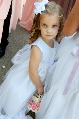 Flower girl with pearls and white bow in curly hair