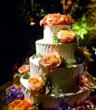 White cake with bright orange fresh roses