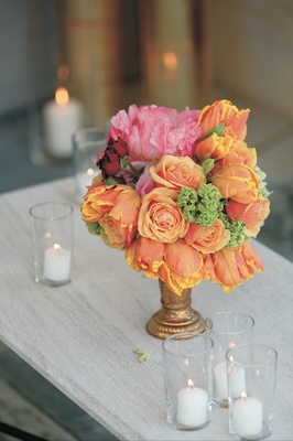 Wedding reception floral arrangement of orange, pink, green, and red flowers in a gold vase