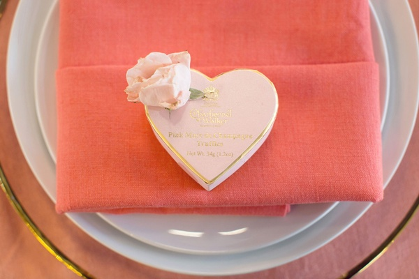 Bridal shower champagne theme pink truffles in heart shape box with flower and coral napkin on plate