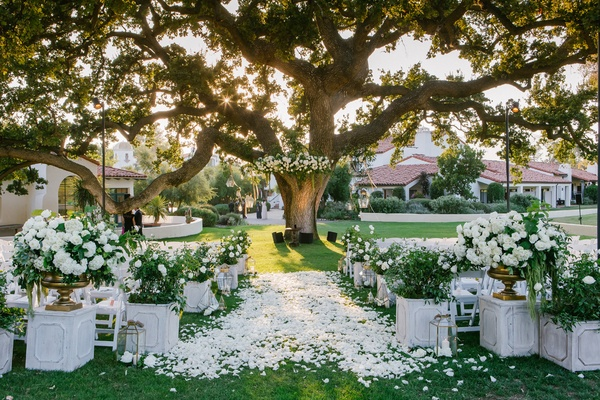 wedding aisle with white rose petals, white and green arragements